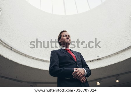 Satisfied happy young businessman standing under dome of light.