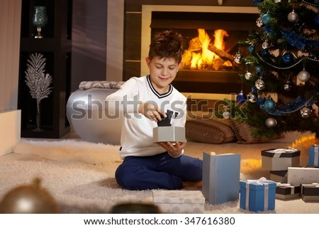 Satisfied little boy opening christmas box with mobilephone, sitting on floor, smiling. - stock photo