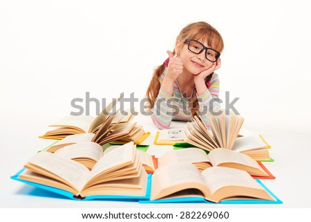 Satisfied little girl lying on stomach on the floor with a lot of opened books in front of her, gesturing thumb up, over white background - stock photo