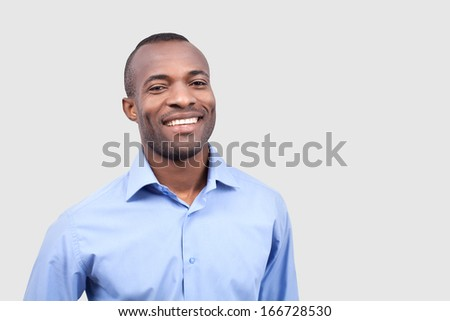 Satisfied man. Cheerful young black man smiling at camera while standing isolated on grey background - stock photo