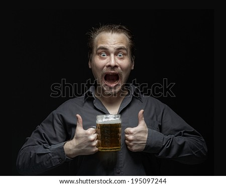 Satisfied man with beer on a dark background. Studio photography. Happy man with a mug of beer.