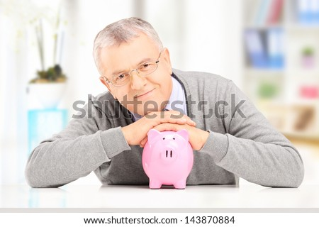 Satisfied mature gentleman posing over a piggy bank at his home - stock photo