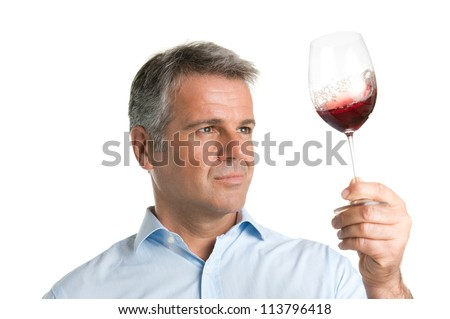 Satisfied mature man looking at red glass of wine during a winetasting - stock photo