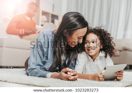 Satisfied mother and child hanging out together. They are relaxing on rug with tablet and looking at each other with joy. Father on background. Focus on females
