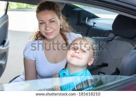 Satisfied mother and little child fastened in safety car seat - stock photo