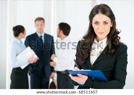 Satisfied smiling business woman compiling a form for a job recruitment or interview at office - stock photo