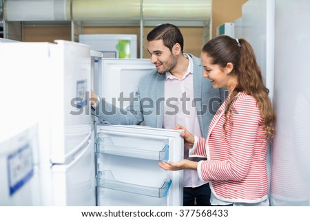 Satisfied smiling couple looking at large fridges in domestic appliances section