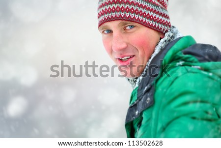 Satisfied smiling man standing in the green jacket outdoors - stock photo