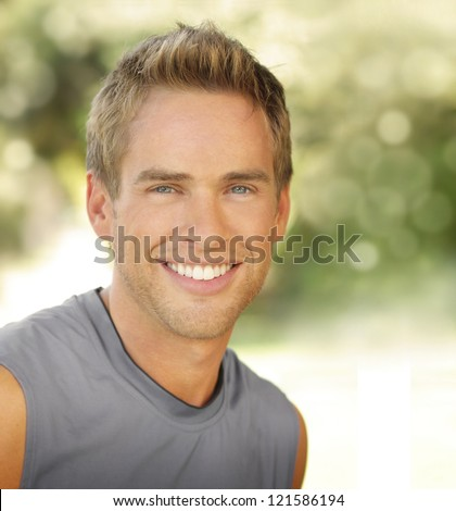 Satisfied smiling young male outdoors with copy space - stock photo