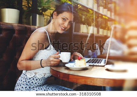 Satisfied successful businesswoman in elegant clothes sitting at cafe table with net-book enjoying a cup of cafe she smile and looks to the camera, young latin female at work break in a coffee shop - stock photo