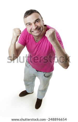 Satisfied successful man in a pink shirt and jeans at full height. Funny perspective from top to bottom - stock photo