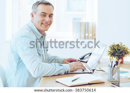 Satisfied with his work. Side view of cheerful mature man working on laptop and looking at camera with smile while sitting at his working place