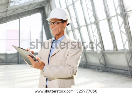Satisfied with results. Cheerful delighted professional architect holding folder and making drawing while being involved in work - stock photo