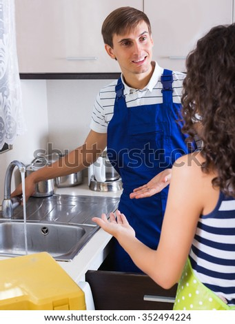 Satisfied woman client thanking professional plumber for work