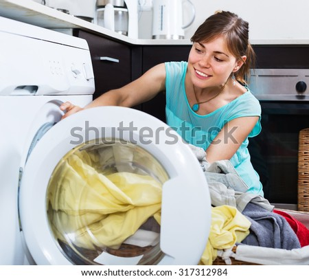 Satisfied woman enjoying clean clothes without stains after laundry - stock photo
