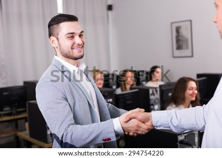 Satisfied young customer service manager shaking hand of employee - stock photo