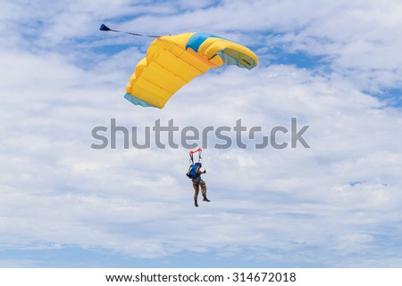 SATTAHIP CHONBURI - SEPTEMBER , 9 :The parachutist descends and trains in landing accuracy that parachute fly on blue sky with white cloud. THAILAND SEPTEMBER,9 2015