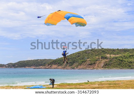 SATTAHIP CHONBURI - SEPTEMBER , 9 :The parachutist descends and trains in landing accuracy that parachute fly down near the sea beach. THAILAND SEPTEMBER,9 2015