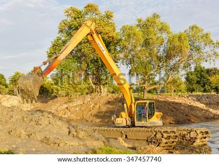 SATTAHIP - DEC,5 : The dirty backhoe working in mud lake in new bridge building site in Pattaya Chonburi. THAILAND DEC,5 2015 - stock photo