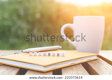 Saturday written in letter beads and a coffee cup on table - stock photo