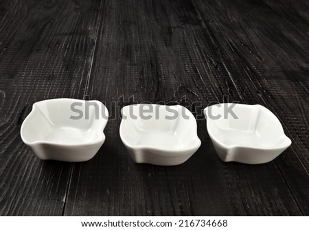Sauce boat on black wooden rustic surface background - stock photo
