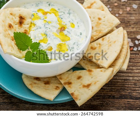Sauce with yogurt and cucumber for starter with slices of bread on a white plate and a dark natural wood background. selective Focus - stock photo