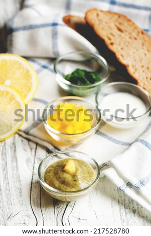 Sauceboats with different sauces and seasonings with lime and bread on white wooden table - stock photo
