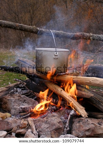 Saucepan on campfire - stock photo