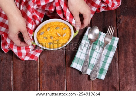 Saucepan with orange pumpkin puree on the table. Female hands and a pot of porridge. Diet lunch. Pumpkin porridge for breakfast. Kitchen table. Tablecloth, pan, cutlery and napkins. - stock photo