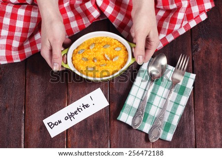 Saucepan with orange pumpkin puree on the table. Kitchen table. Tablecloth, pan, cutlery and napkins. Female hands and a pot of porridge. Diet lunch. Pumpkin porridge for breakfast. - stock photo