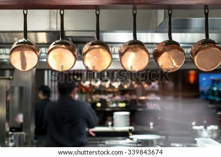 saucepans hanging from a rack in busy kitchen - stock photo
