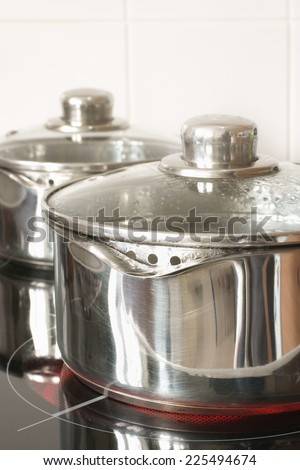 Saucepans on an electric glass top halogen cooker hob - stock photo