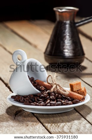Saucer with a cup for espresso and grains coffee and cinnamon against coffee top on a wooden table. - stock photo