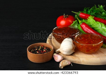 sauces in a glass bowl near the leaves are green with heads of garlic and with spices and vegetables on black wood background