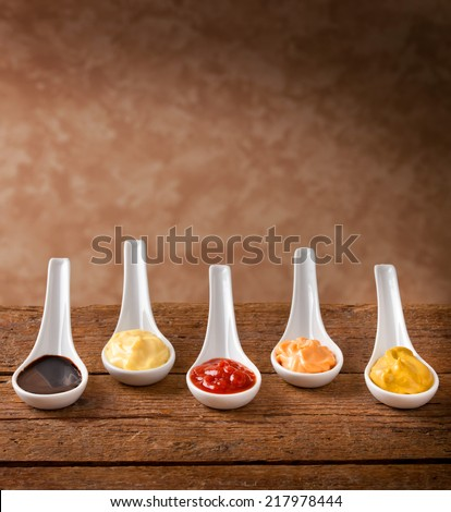 Sauces mixed in the ceramic spoons on wooden table - stock photo