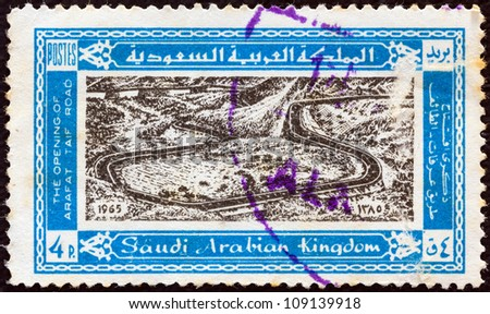 SAUDI ARABIA - CIRCA 1965: A stamp printed in Saudi Arabia issued for the opening of highway from Mecca to Tayif shows the highway, Hejaz Mountains, circa 1965. - stock photo