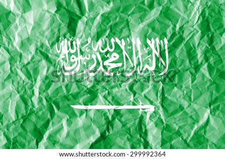 Saudi Arabia flag painted on crumpled paper background. - stock photo