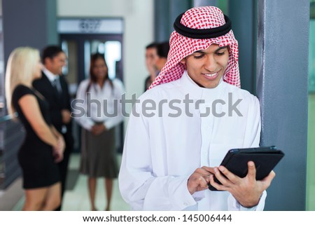 saudi arabian businessman using tablet computer in modern office - stock photo