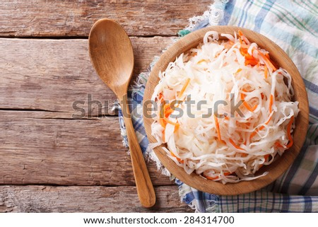 sauerkraut and carrots in a wooden plate. horizontal view from above, rustic style