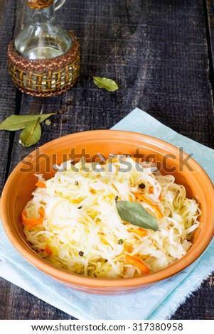 Sauerkraut in a bowl on a wooden table - stock photo