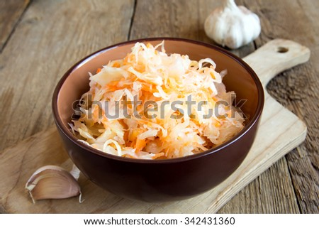 Sauerkraut in ceramic bowl on rustic wooden table with garlic, traditional rustic winter food - stock photo