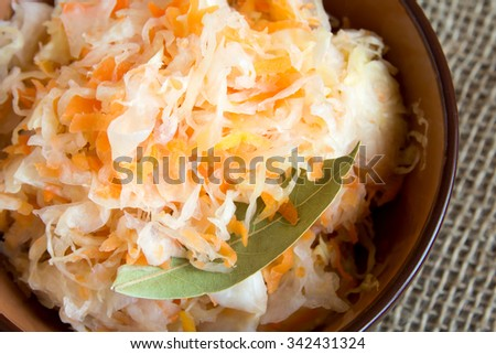 Sauerkraut in ceramic bowl on rustic wooden table with spices, traditional rustic winter food