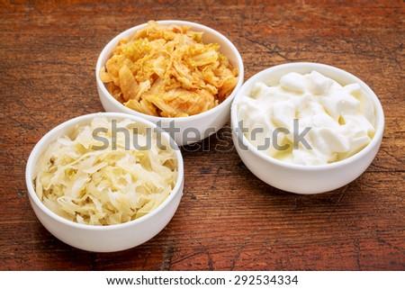 sauerkraut, kimchi and yogurt - popular probiotic fermented food - three ceramic bowl against rustic wood - stock photo