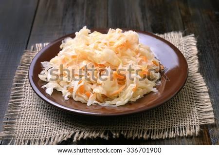 Sauerkraut on ceramic plate on wooden table - stock photo