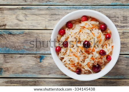 Sauerkraut or sour cabbage with cranberries in a white bowl on rustic wooden table, rural style, top view - stock photo