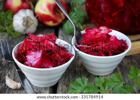 Sauerkraut with beets and garlic on a wooden table - stock photo