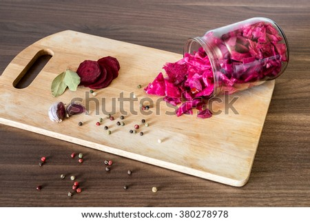 sauerkraut with beets and spices in a glass jar on wooden background - stock photo