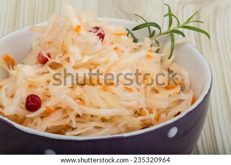 Sauerkraut with berries in the bowl on wooden background