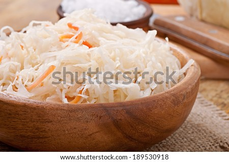 Sauerkraut with carrot in wooden bowl - stock photo