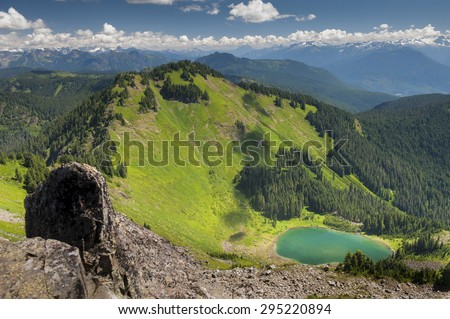 Sauk Mountain, Washington, USA. The North Cascade mountain range in its full glory with a 360 degree view of the entire western Washington landscape. Wildflowers are in bloom on this warm summer day. - stock photo